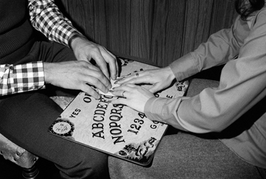 Using Ouija Board --- Image by © Bettmann/CORBIS